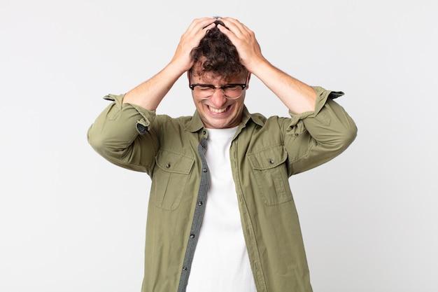 Junger gutaussehender mann, der sich gestresst und frustriert fühlt, die hände zum kopf hebt, sich müde, unglücklich und mit migräne fühlt