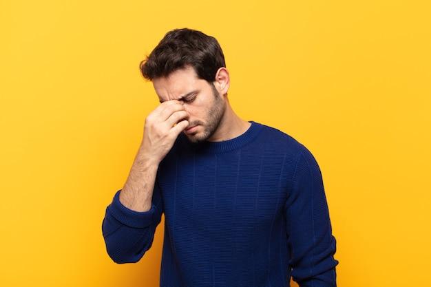 Junger gutaussehender mann, der sich gestresst, unglücklich und frustriert fühlt, die stirn berührt und unter migräne mit starken kopfschmerzen leidet