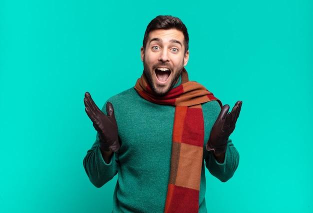 Junger gutaussehender mann, der sich glücklich, aufgeregt, überrascht oder schockiert fühlt, lächelt und erstaunt über etwas unglaubliches. kalt und winter concetp