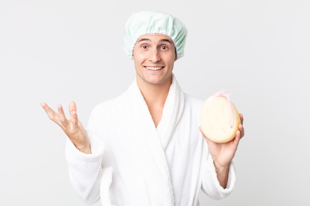 Junger gutaussehender mann, der sich glücklich fühlt, überrascht, eine lösung oder idee mit bademantel, duschhaube und schwamm zu realisieren