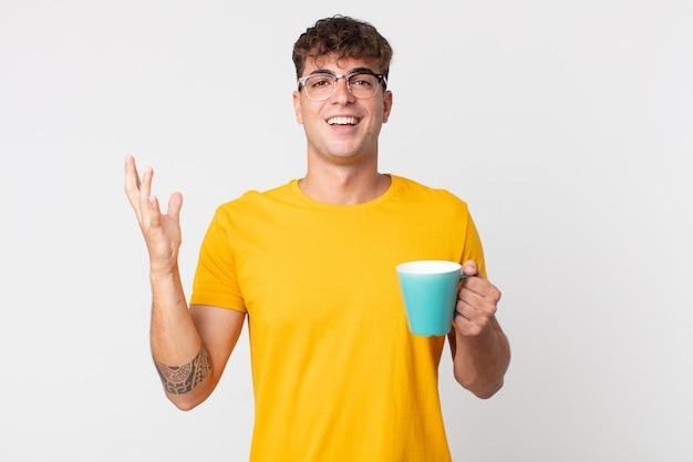 Junger gutaussehender mann, der sich glücklich fühlt, überrascht, eine lösung oder idee zu erkennen und eine kaffeetasse zu halten