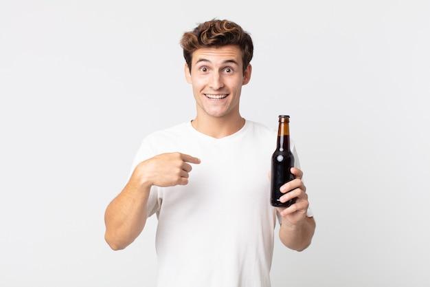 Junger gutaussehender mann, der sich glücklich fühlt und auf sich selbst zeigt, aufgeregt und hält eine bierflasche