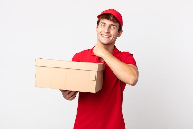 Junger gutaussehender mann, der sich glücklich fühlt und einer herausforderung gegenübersteht oder das konzept des lieferpaketservice feiert.