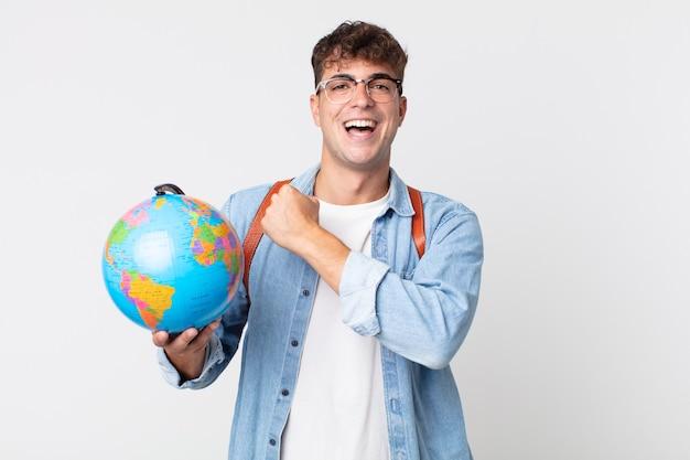 Junger gutaussehender mann, der sich glücklich fühlt und einer herausforderung gegenübersteht oder feiert. student, der eine weltkugelkarte hält