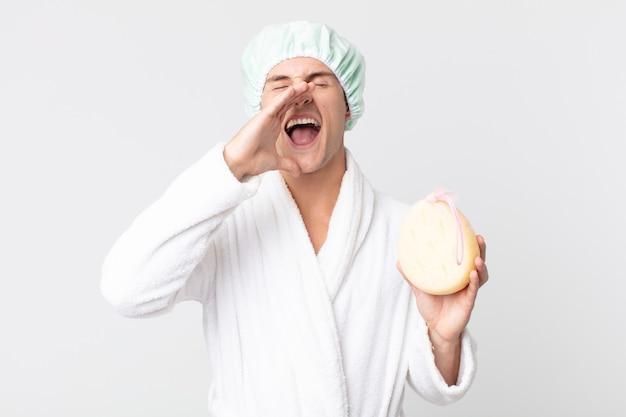 Junger gutaussehender mann, der sich glücklich fühlt und mit den händen neben dem mund mit bademantel, duschhaube und schwamm einen großen schrei ausspricht