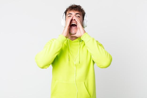 Junger gutaussehender mann, der sich glücklich fühlt und mit den händen neben dem mund und den kopfhörern einen großen schrei ausstößt
