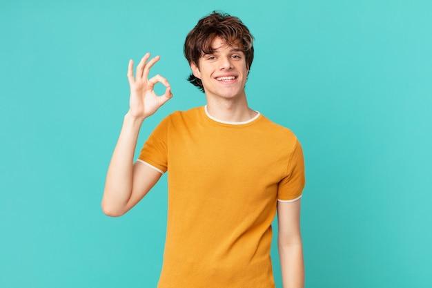 Junger gutaussehender mann, der sich glücklich fühlt und zustimmung mit einer okayen geste zeigt