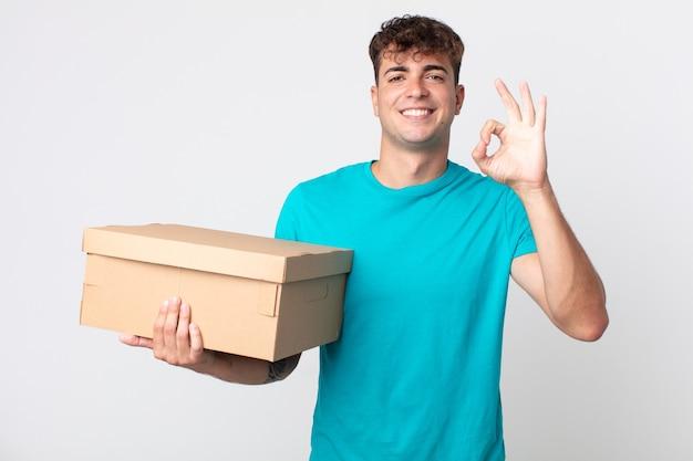 Junger gutaussehender mann, der sich glücklich fühlt, zustimmung mit okayer geste zeigt und einen karton hält