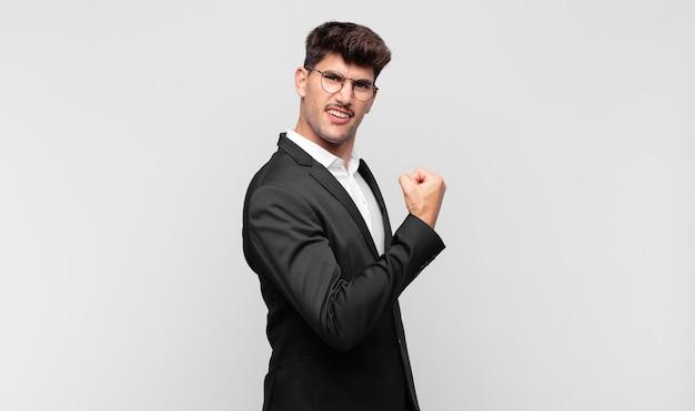 Junger gutaussehender mann, der sich glücklich, zufrieden und kraftvoll fühlt, die passform und den muskulösen bizeps beugt und stark nach dem fitnessstudio schaut