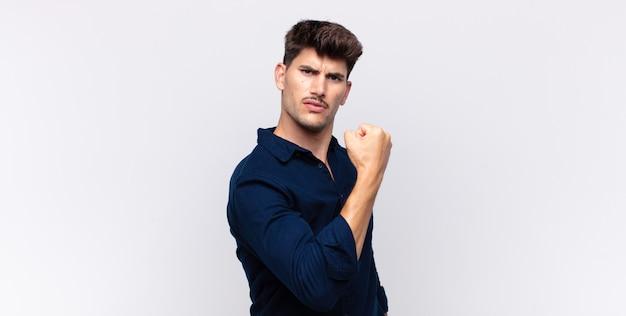 Junger gutaussehender mann, der sich glücklich, zufrieden und kraftvoll fühlt, fit und muskulös ist und nach dem fitnessstudio stark aussieht