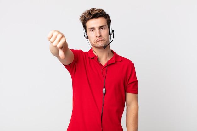 Junger gutaussehender mann, der sich kreuz fühlt und daumen nach unten zeigt. telemarketing-konzept