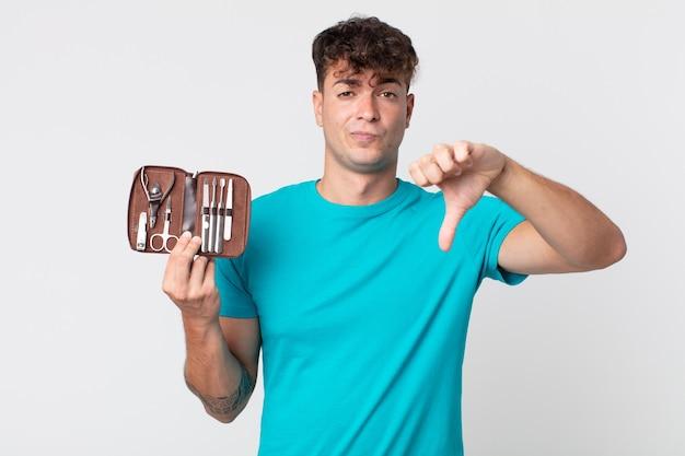 Junger gutaussehender mann, der sich kreuzen lässt, daumen nach unten zeigt und einen nagelwerkzeugkoffer hält