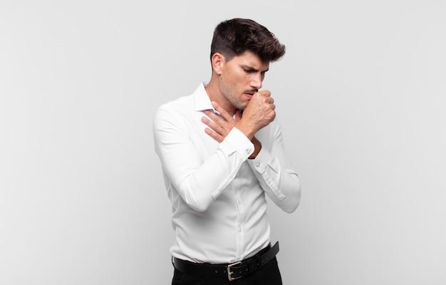 Junger gutaussehender mann, der sich mit halsschmerzen und grippesymptomen krank fühlt und mit bedecktem mund hustet