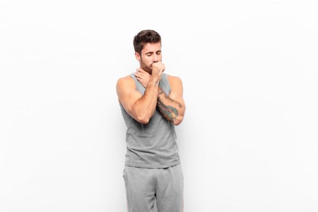 Junger gutaussehender mann, der sich mit halsschmerzen und grippesymptomen krank fühlt und mit mundkegel hustet. sportkonzept