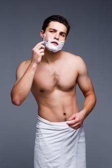 Junger gutaussehender mann, der sich morgens rasiert und auf grauer wand bleibt