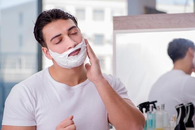 Junger gutaussehender mann, der sich morgens rasiert