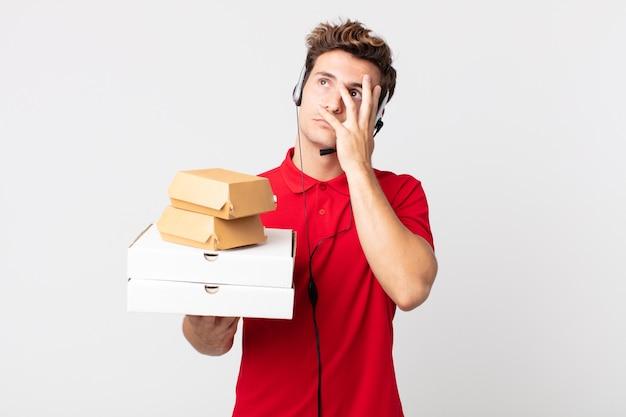 Junger gutaussehender mann, der sich nach einem ermüdenden gefühl gelangweilt, frustriert und schläfrig fühlt. take-away-fast-food-konzept