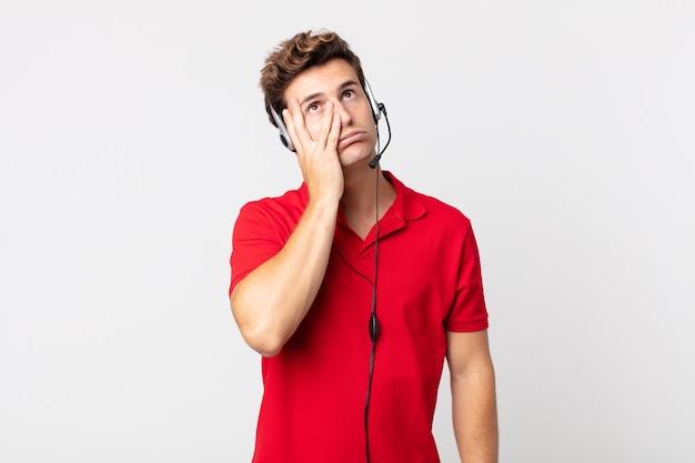 Junger gutaussehender mann, der sich nach einem ermüdenden gefühl gelangweilt, frustriert und schläfrig fühlt. telemarketing-konzept