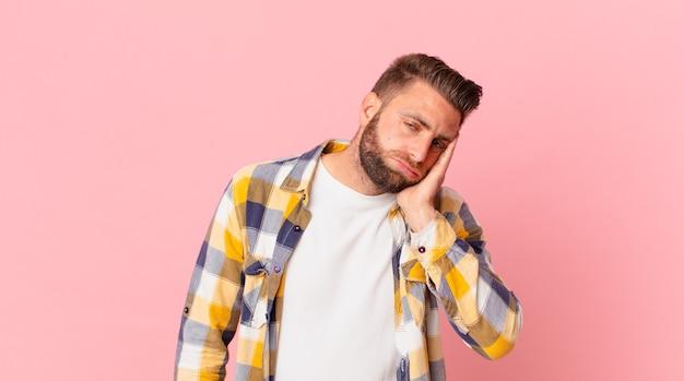 Junger gutaussehender mann, der sich nach einem ermüdenden gefühl gelangweilt, frustriert und schläfrig fühlt