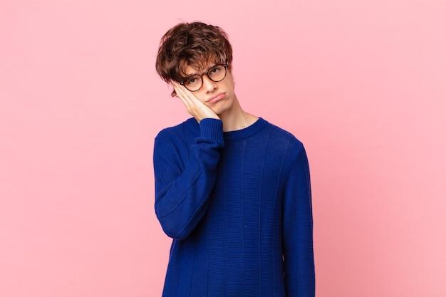 Junger gutaussehender mann, der sich nach einem ermüdenden gelangweilt, frustriert und schläfrig fühlt