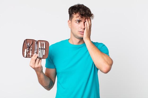 Junger gutaussehender mann, der sich nach einem ermüdenden und halten eines nagelwerkzeugkoffers gelangweilt, frustriert und schläfrig fühlt