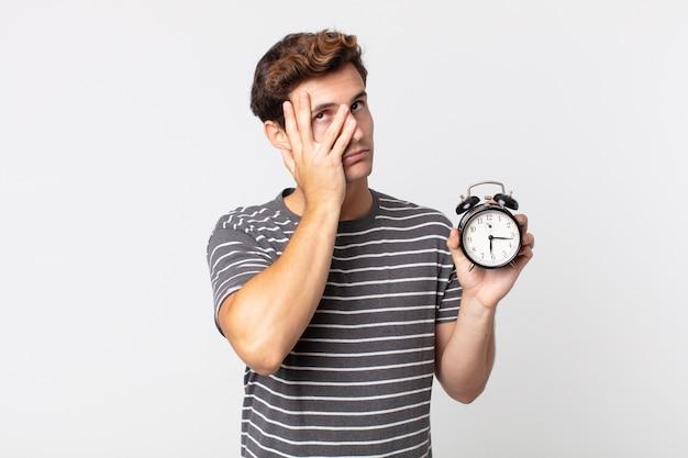 Junger gutaussehender mann, der sich nach einem ermüdenden und halten eines weckers gelangweilt, frustriert und schläfrig fühlt