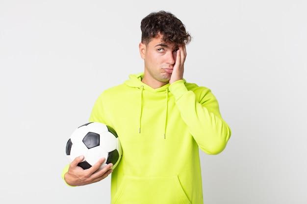 Junger gutaussehender mann, der sich nach einem ermüdenden und mit einem fußball haltenden ball gelangweilt, frustriert und schläfrig fühlt