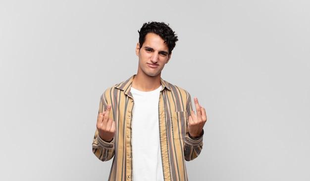 Junger gutaussehender mann, der sich provokativ, aggressiv und obszön fühlt, den mittelfinger dreht, mit einer rebellischen haltung