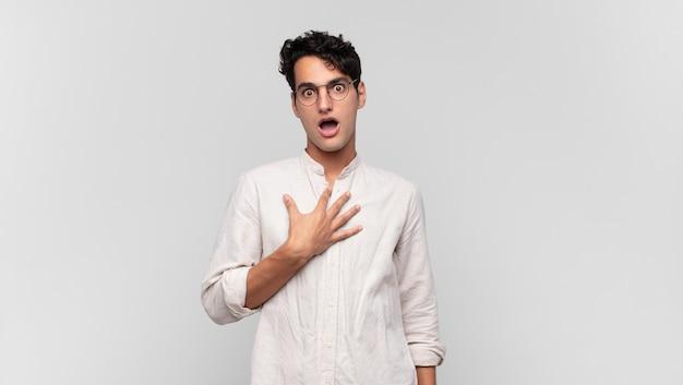 Junger gutaussehender mann, der sich schockiert, erstaunt und überrascht fühlt, mit der hand auf der brust und dem offenen mund und sagt, wer, ich?