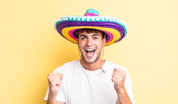 Junger gutaussehender mann, der sich schockiert fühlt, lacht und erfolg feiert. mexikanisches hutkonzept