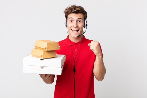Junger gutaussehender mann, der sich schockiert fühlt, lacht und erfolg feiert. take-away-fast-food-konzept