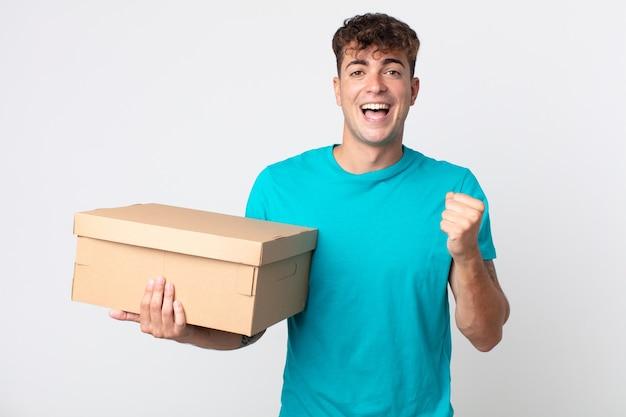 Junger gutaussehender mann, der sich schockiert fühlt, lacht und erfolg feiert und einen karton hält