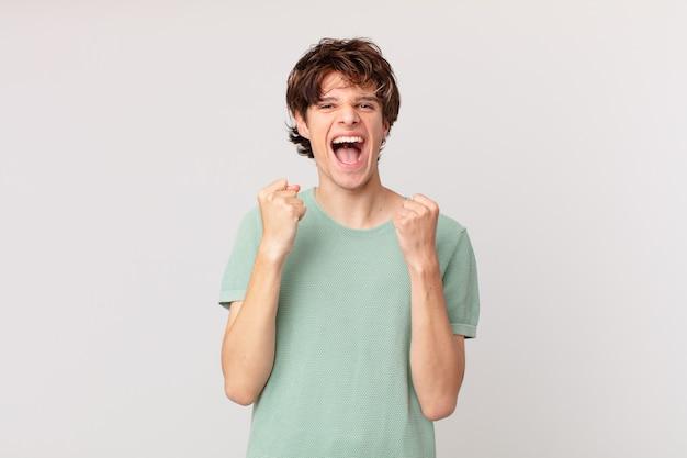 Junger gutaussehender mann, der sich schockiert fühlt, lacht und erfolg feiert