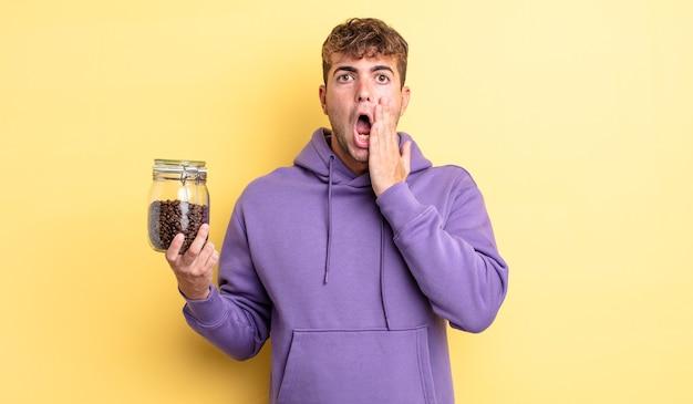 Junger gutaussehender mann, der sich schockiert und verängstigt fühlt. kaffeebohnen-konzept