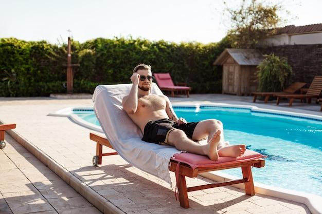 Junger gutaussehender mann, der sich sonnt und auf chaiselongue nahe schwimmbad liegt
