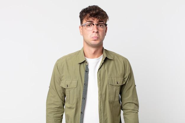 Junger gutaussehender mann, der sich traurig und gestresst fühlt, verärgert wegen einer bösen überraschung, mit einem negativen, ängstlichen blick