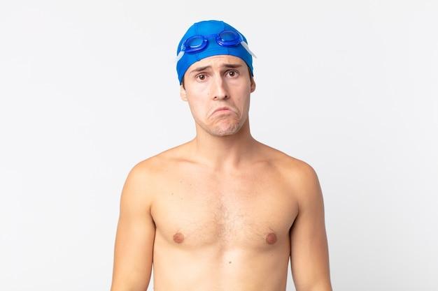 Junger gutaussehender mann, der sich traurig und weinerlich mit einem unglücklichen blick und weinen fühlt. schwimmer-konzept