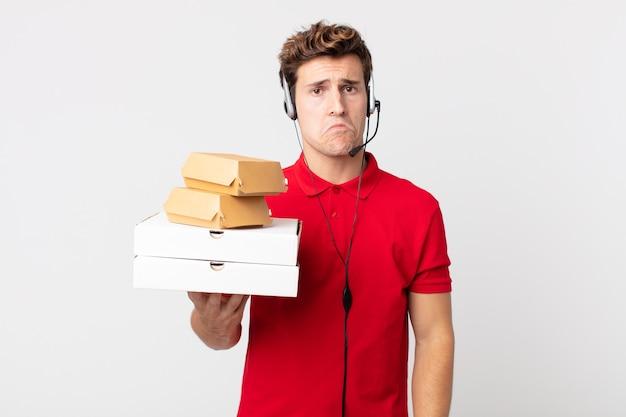 Junger gutaussehender mann, der sich traurig und weinerlich mit einem unglücklichen blick und weinen fühlt. take-away-fast-food-konzept