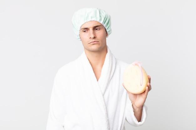 Junger gutaussehender mann, der sich traurig, verärgert oder wütend fühlt und mit bademantel, duschhaube und schwamm zur seite schaut