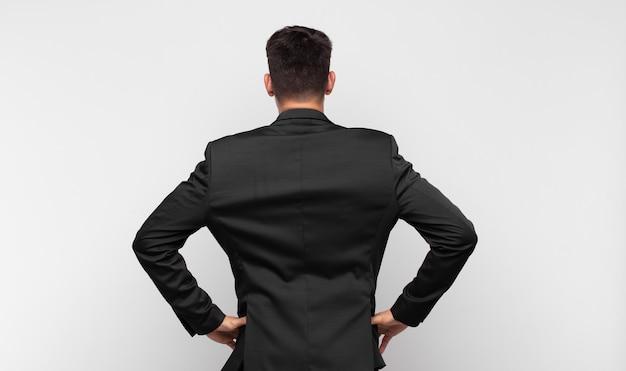 Junger gutaussehender mann, der sich verwirrt oder voll fühlt oder zweifel und fragen hat, sich wundert, mit den händen auf den hüften, rückansicht