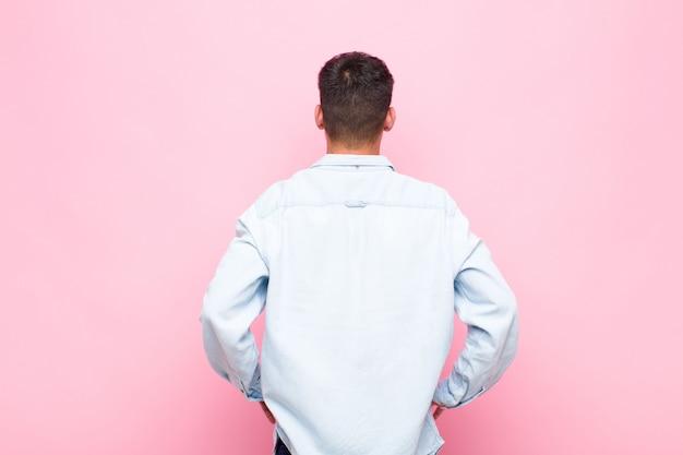 Junger gutaussehender mann, der sich verwirrt oder voll oder zweifel und fragen fühlt und sich wundert, mit händen auf den hüften, rückansicht über rosa wand