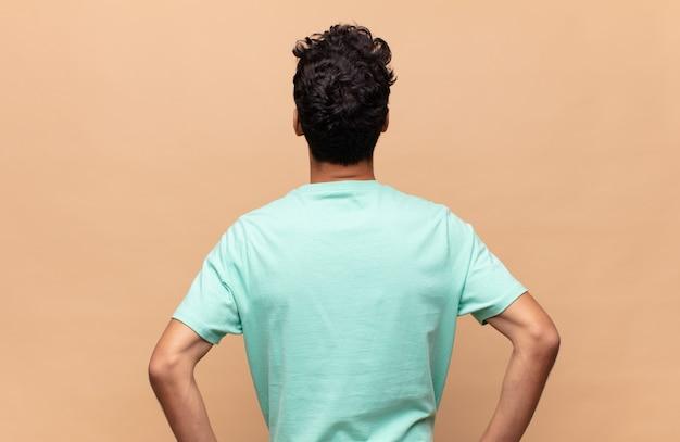 Junger gutaussehender mann, der sich verwirrt oder voll oder zweifel und fragen fühlt und sich wundert, mit händen auf den hüften, rückansicht