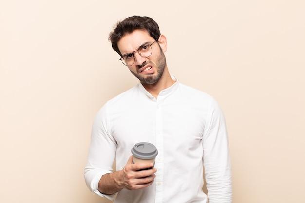 Junger gutaussehender mann, der sich verwirrt und verwirrt fühlt, mit einem stummen, fassungslosen ausdruck, der etwas unerwartetes ansieht