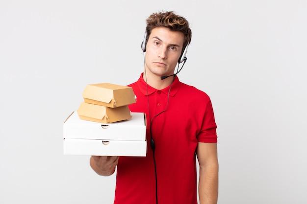 Junger gutaussehender mann, der sich verwirrt und verwirrt fühlt. take-away-fast-food-konzept