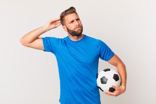 Junger gutaussehender mann, der sich verwirrt und verwirrt fühlt und den kopf kratzt. fußballkonzept