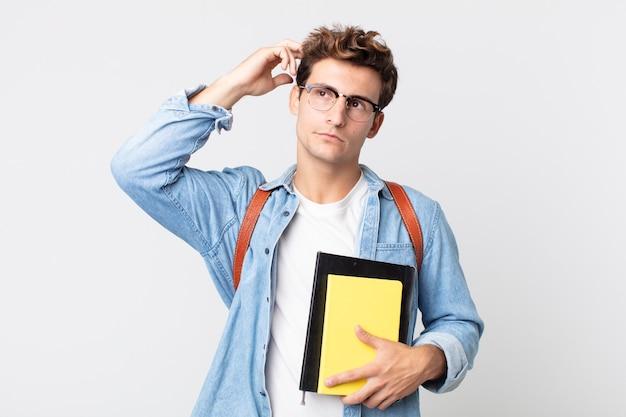 Junger gutaussehender mann, der sich verwirrt und verwirrt fühlt und den kopf kratzt. konzept für universitätsstudenten