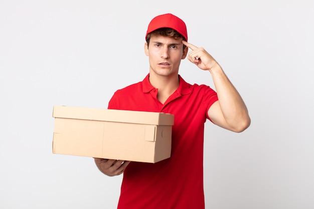 Junger gutaussehender mann, der sich verwirrt und verwirrt fühlt und zeigt, dass sie ein verrücktes paketdienstkonzept sind.