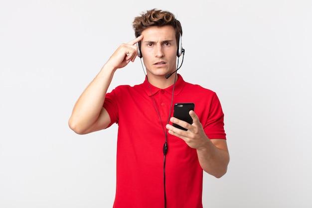 Junger gutaussehender mann, der sich verwirrt und verwirrt fühlt und zeigt, dass sie mit einem smartphone und einem headset verrückt sind