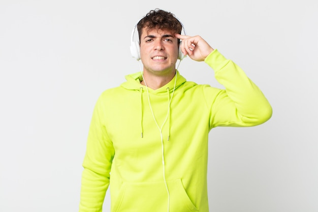 Junger gutaussehender mann, der sich verwirrt und verwirrt fühlt und zeigt, dass sie verrückt sind und kopfhörer?