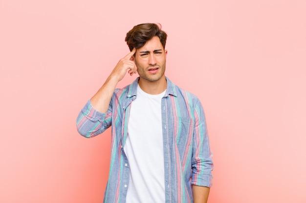 Junger gutaussehender mann, der sich verwirrt und verwirrt fühlt und zeigt, dass sie verrückt, verrückt oder verrückt nach rosa wand sind